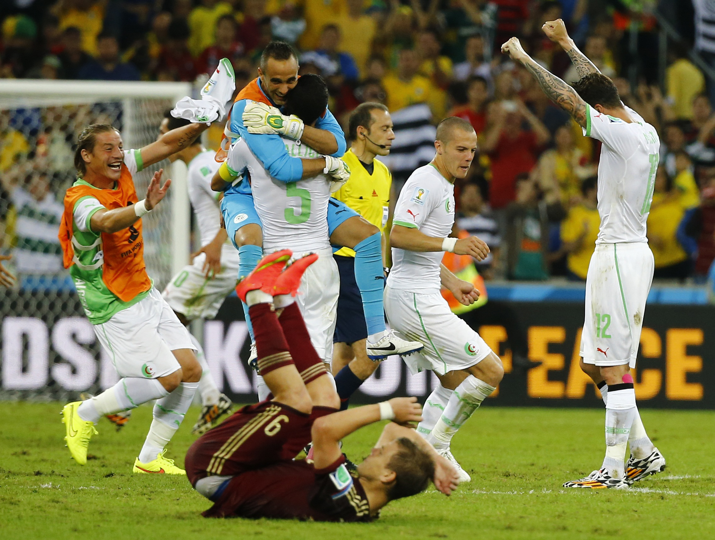 Russia's Kokorin reacts on the ground as Algeria's national soccer team players celebrate behind him at the end of their 2014 World Cup Group H soccer match at the Baixada arena in Curitiba
